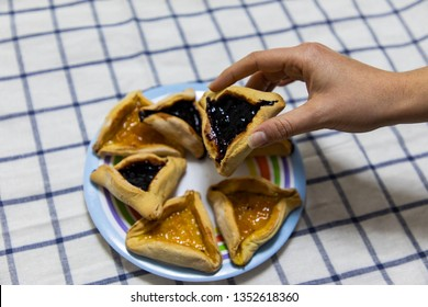 woman hand holding Hamantash Purim Blueberry and apricot jam cookies on colored plate on blue and white tablecloth