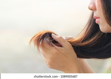 Woman hand holding her long hair with looking at damaged splitting ends of hair care problems