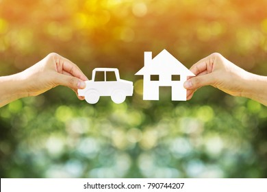 Woman hand holding home and car with paper art filed together on bokeh background in the public park, Loans for buying a house vs buying a car before anything good concept.