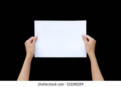 Woman hand holding horizontal sheet of paper isolated on black background.