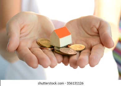 Woman hand holding house and money suggesting the rising cost of home prices
