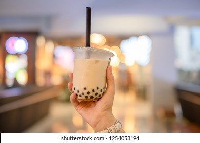 woman hand holding iced milk bubble tea with tapioca pearls, traditional drink of Taiwan