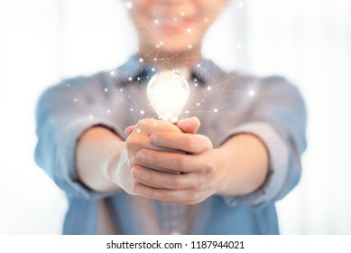 Woman hand holding illuminated light bulb, concept of idea and creativity and innovation.