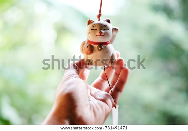Woman hand is holding a Japanese lucky cat doll is hanging on the window