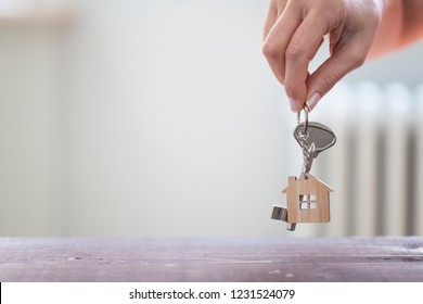 Woman hand holding key with house shaped keychain. Mortgage concept. Natural light room interior. Real estate, moving home or renting property.
