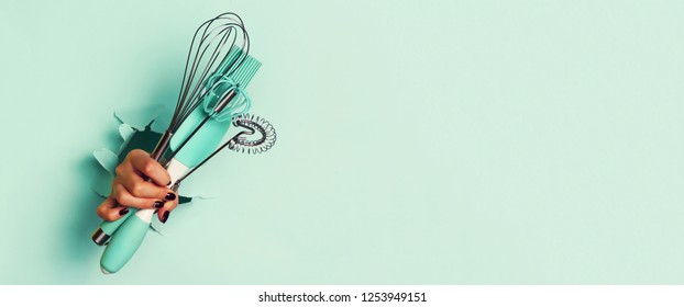Woman hand holding kitchen utensils on blue background. Baking tools - brush, whisk, spatula. Bakery, cooking, healthy homemade food concept. Copy space.
