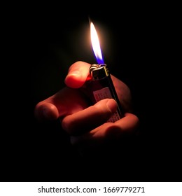 Woman Hand Holding Lit Lighter in the dark