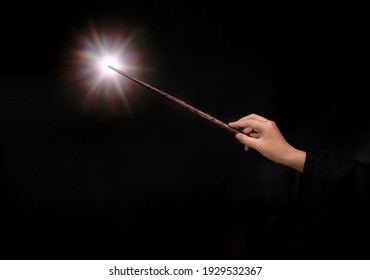 Woman hand holding Magic wand on Purple black background, Miracle magical stick Wizard tool on black. - Shutterstock ID 1929532367