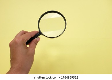Woman hand holding magnifying glass on yellow background