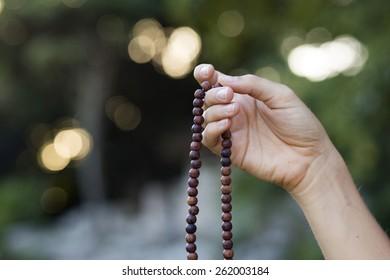 Woman hand holding mala beads for prayer and meditation