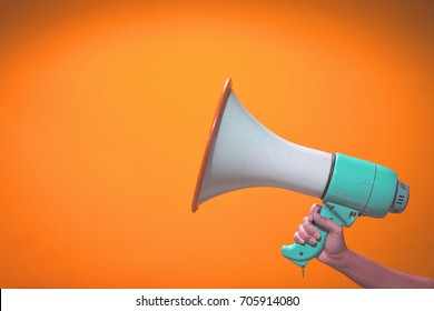 woman hand is holding megaphone on orange background,announcement concept,closed up, copy space