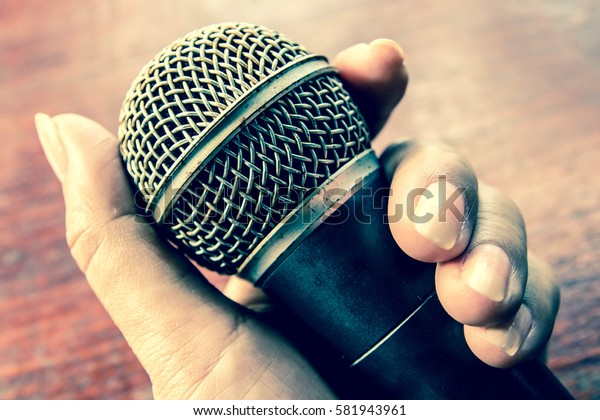 Woman hand holding a microphone,Old microphone