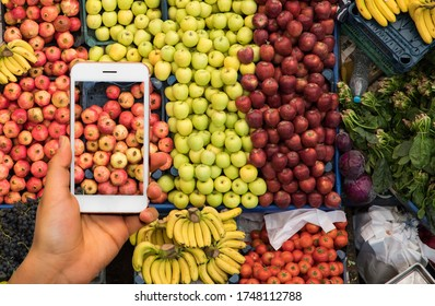 woman hand holding mobile phone pay market fruits, vegetables Konya, Turkey - 13 10 2018