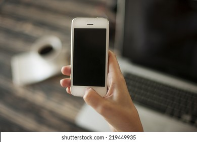 Woman hand holding mobile phone, and laptop and coffee cup