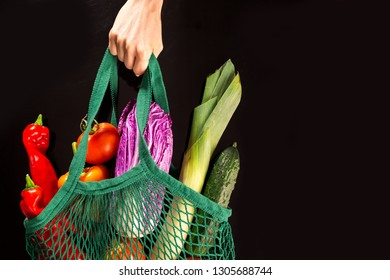 Woman hand holding net bag with vegetable over black background