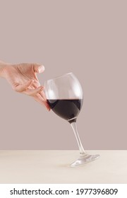 Woman hand holding on glass of red wine. Stylish minimal aesthetic.