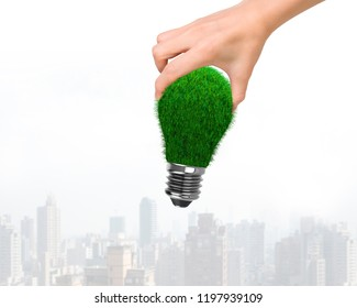 Woman hand holding one light bulb with green grass, on city buildings skyscrapers background, concept of ECO and green energy.