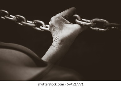 Woman hand holding onto a stainless steel chain. Woman's struggle concept idea