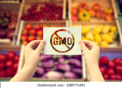 Woman hand holding a paper sheet  with no gmo sign over vegetables blurred background.Natural Eco  Food Products.Bio Concept.