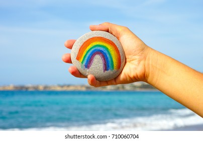 Woman hand holding pebble with painted rainbow against blue sky and sea.