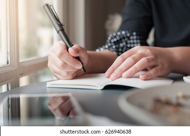 Woman hand holding pen while writing on small notebook beside window. Freelance journalist working at home concept.