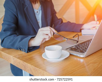 Woman hand holding pen while using touchpad of laptop