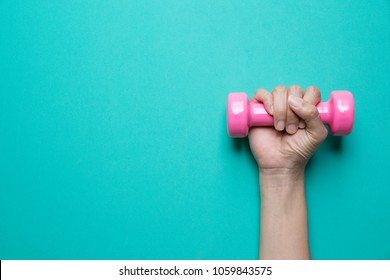 woman hand holding pink dumbbell on green background
