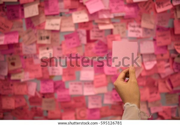 Woman hand holding pink  sticky note
