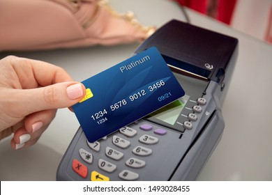 Woman hand holding plastic card and pay pass online terminal shopping at a store