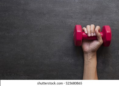woman hand holding red dumbbell on black background