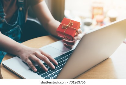 Woman hand holding red gift box about shopping online concept.