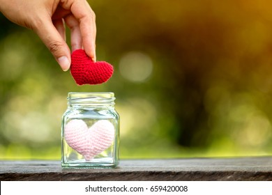 Woman hand holding a red heart with love put in the glass jar on the wooden vintage in public park, for supporting when people get who lack of desire with love concept.