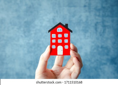 woman hand holding red home model on blue background, business and finance concept