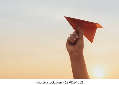 Woman Hand holding red paper rocket with blue sky background. freedom concept.