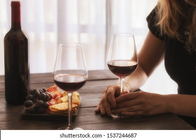 Woman hand holding red wine glass in the restaurant. Wine lover and romantic dinner concept. Lifestyle image.