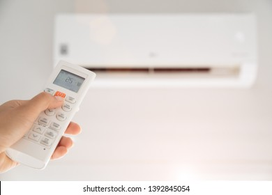 woman hand holding remote controller directed on the air conditioner inside the room and set at ambient temperature,25 degrees celsius.