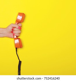 Woman hand holding retro orange phone tube against yellow background - Flat lay