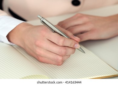 Woman hand holding silver pen ready to make note in opened notebook. Businesswoman or employee at workplace writing business ideas, plans, tasks at personal organizer. Office life or education concept