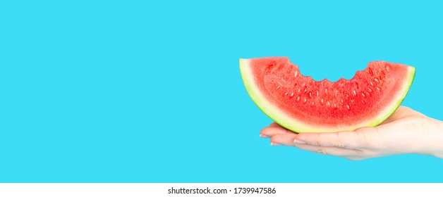 A woman hand holding a slice of watermelon on a blue background. Long banner