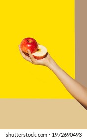 Woman hand holding sliced red apple against yellow background. Vibrant bold colors. Minimal food concept.