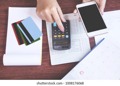 woman hand holding smart phone calculating her monthly expenses with credit card,saving account book, deadline calendar concept for shopping online,payment and dept collection