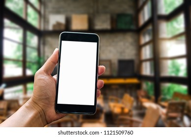 A woman hand holding smart phone device in the coffee shop or cafe background.