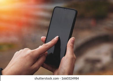 woman hand holding smart phone outside and touching screen.