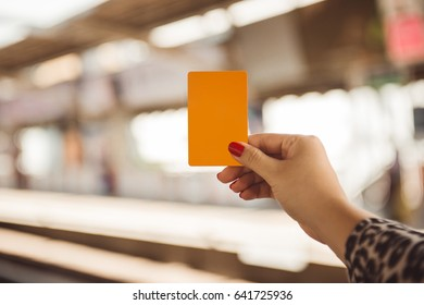 Woman hand holding smartcard for mrt or train on blurred of train station