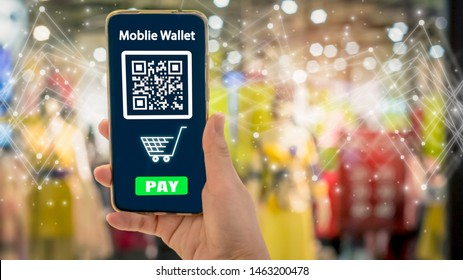 woman hand holding smartphone with blurred shop background, with mobile wallet electronic and shopping online concept,with Qr code payment on screen, E wallet and cashless society technology