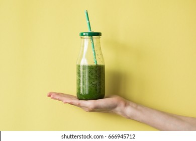 Woman hand holding smoothie shake against colored wall. Drinking green healthy smoothie concept.