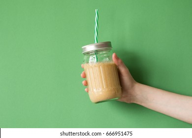 Woman hand holding smoothie shake against colored wall. Drinking yellow healthy smoothie concept.