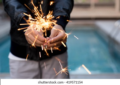 Woman hand holding sparkler outdoors with swimming pool in background