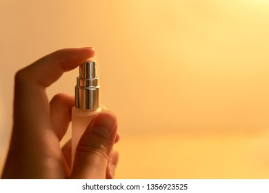 Woman hand holding spray bottle with warm yellow light background.