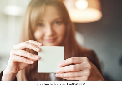 Woman hand holding square blank clean sticker mock up. Close up background place for text